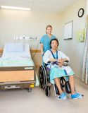 Male Patient Sitting On Wheelchair While Nurse Stock Images