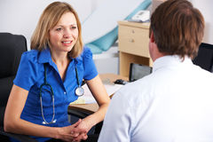Male patient speaking with female doctor Stock Photography