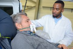 Male patient on stretcher wearing oxygen mask. Oxygen stock image