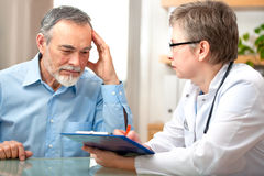 Doctor and patient. Male patient tells the doctor about his health complaints Stock Image