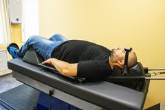 Male patient on treatment of intervertebral discs and spinal hernia, stretching spine on special medical machine tool. Modern physical therapy of neck, health royalty free stock photos