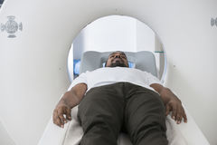 Male Patient Undergoing CT Scan In Examination Room. Mid adult male patient undergoing CT scan in examination room Stock Images