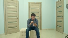 Male patient using phone while waiting for his doctor appointment