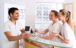 Male patient visiting medical clinic. Smiling young guy talking with cheerful young nurses in medical clinic royalty free stock image