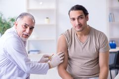 Male patient visitng doctor for shot inoculation. The male patient visitng doctor for shot inoculation stock photos