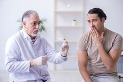 The male patient visitng doctor for shot inoculation royalty free stock photos