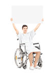 Male patient in a wheelchair holding a blank panel Royalty Free Stock Image