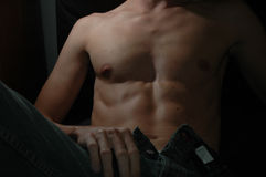 Male pecks in jeans. On a black background Royalty Free Stock Photo
