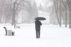 Male pedestrian hiding from the snow under umbrella Stock Photo