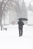 Male pedestrian hiding from the snow under umbrella, vertical Stock Photo