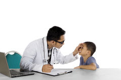 Male pediatrician is checking his patient eyes Royalty Free Stock Image