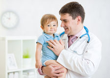 Male pediatrician holding baby boy patient Stock Photo