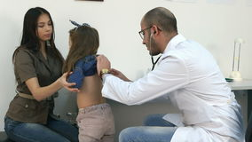 Male pediatrician with stethoscope listening to little girl chest and back stock video footage