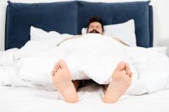 Male pedicure En vilken stora morgon s?mnig man i sovrum mans?mn i morgon Energi sovande och vaket man i s?ng royaltyfri foto