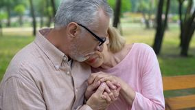 Male pensioner holding sad wife hands, health problem, spouse support, care. Stock photo royalty free stock photos