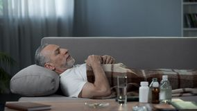 Male pensioner sleeping in bed after taking medicaments, illness and healthcare. Stock footage Royalty Free Stock Image
