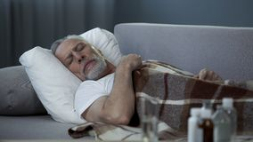 Male pensioner sleeping on couch, suffering from high temperature, disease. Stock footage Stock Photo