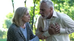 Male pensioner suffering from heart attack, retired couple walking in park stock photography