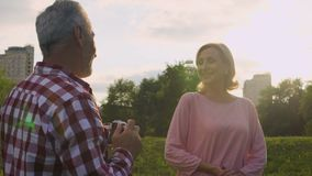 Male pensioner taking picture of attractive senior woman in park, hobby, date