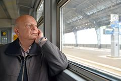 The male pensioner thoughtfully looks out of the electric train. Window Royalty Free Stock Photography