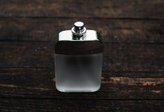 Male perfume over wooden background. Bottle of modern male perfume on dark wooden background Royalty Free Stock Image