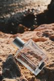 Male Perfume and yellow rocks on the beach royalty free stock photography