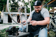 Male person adjusts bike spokes and wheel. Male person in apron adjusts bike spokes and wheel with service tools. Cycle workshop outdoor. Bicycling sport Stock Photography
