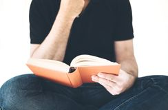 Male person in casual clothing sitting cross legged reading a book. Male person in casual clothing sitting cross legged reading a hardcover book Stock Photography