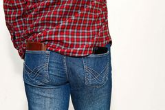 Person in checkered shirt with money in back pocket. Male person in checkered classic work shirt and blue jeans. Leather wallet and cell phone unsafe stick out Stock Photography