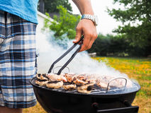 Male person with food tweezers barbequing Stock Images