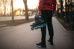 Male person hands with roller skates. City park on background. Male rollerskater with rollerskates Royalty Free Stock Image