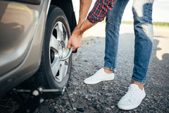 Male person hands with wheel wrench, broken car Stock Photos
