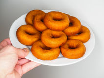 Male person holding a plate of freshly made brown doughnuts. Male person holding a plate of freshly made dark brown doughnuts Royalty Free Stock Photography