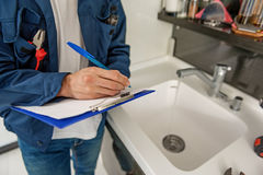 Male person keeping blue clipboard. Handyman is holding folder with paper and writing. He standing near sink. Top view Royalty Free Stock Photography