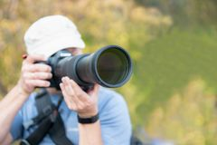 Male person with long telephoto lens stock photo