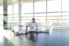 Man doing vigorous movements and swipe. Male person making swipe and vigorous movements in white shirt and pants. Blonde dancer training at studio with large Royalty Free Stock Photo