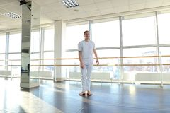 Man doing vigorous movements and swipe. Male person making swipe and vigorous movements in white shirt and pants. Blonde dancer training at studio with large Royalty Free Stock Photography