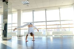 Man doing vigorous movements and swipe. Male person making swipe and vigorous movements in white shirt and pants. Blonde dancer training at studio with large Stock Images