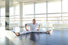 Man doing vigorous movements and swipe. Male person making swipe and vigorous movements in white shirt and pants. Blonde dancer training at studio with large Stock Photography