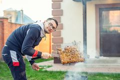 Male person preparing chicken wings on grill at open fire brazier. Barbecue  friens home party at house backyard. Weeken bbq royalty free stock image