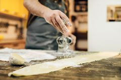 Male person preparing dough, pasta cooking process. Male person in apron preparing dough on wooden kitchen table. Homemade pasta cooking process Royalty Free Stock Images
