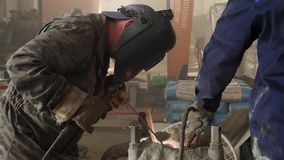 Male person in protective mask welding metall construction, concept of manufactory. Frame. Close up of welder working in