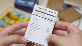 Male Person Reads Food Labels with Nutrition and Quality