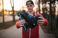 Male person shows roller skates. City park on background. Male rollerskater with rollerskates Royalty Free Stock Photo
