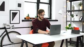 Serious man typing on the laptop sitting in office. Male person sit in art workspace and writing financial report use the desktop pc on the table. Guy type stock video footage