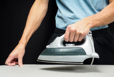 Male person using a steaming hot iron Stock Photo