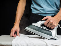 Male person using a steaming hot iron Stock Images