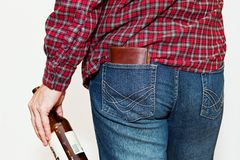 Person in work shirt with beer. Male person wearing classic worn blue jeans and work checkered shirt holding a bottle of beer in his hand. Leather wallet unsafe Stock Images