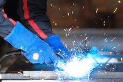 Male person wearing construction gloves welding metall construction, blue welding arc. stock photos