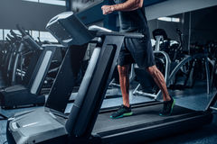 Male person workout on running exercise machine Royalty Free Stock Photography